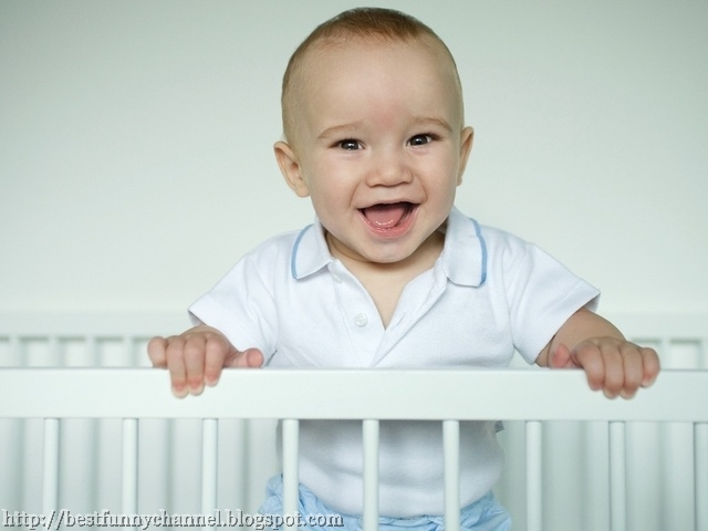Laughing baby in the crib.