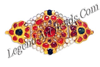 Gold encrusted with rubies, emeralds and colourless sapphires; the original centre-piece was converted to a brooch by Cartier in the early 20th century, when diamond insets, pearls and two black beads were added.