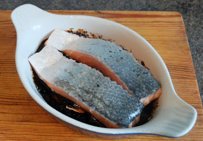 two portions of salmon marinating in a dish