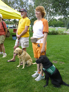 Two Southwest Brighteyes puppy raisers pose with their guide puppies.