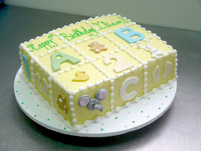 Square baby shower cake with letters and numbers on its surface