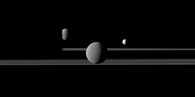 The Cassini spacecraft observes three of Saturn's moons set against the darkened night side of the planet. Image credit: NASA/JPL-Caltech/Space Science Institute