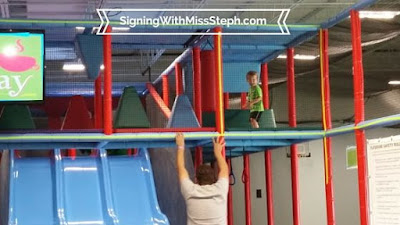 Child running on bridge in 2-story play structure with triple wide slide