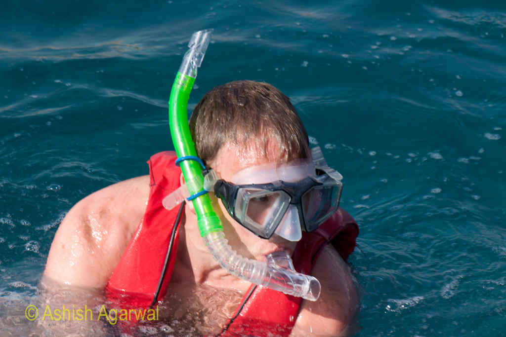 Man wearing the snorkeling equipment including the life vest, with the head out of the water