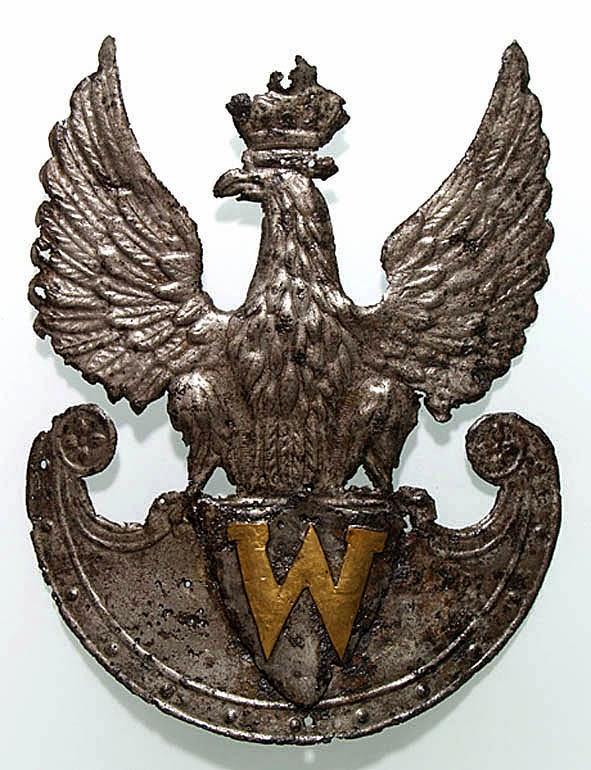 Orzeł na czapkę Korpusu Weteranów z okresu Królestwa Polskiego i powstania Listopadowego. Orzeł noszony był w Korpusie Weteranów - formacji złożonej z wysłużonych ale sprawnych żołnierzy i oficerów. W sytuacji, gdy służba wojskowa trwała wiele lat często ludzie tacy nie potrafili odnaleźć się w życiu cywilnym, nie posiadając środków utrzymania ani majątku. Z tego powodu we wszystkich państwach tworzono formacje które zapewniały opiekę i wsparcie starym wiarusom (ale tylko tym zasłużonym). W zamian pełnili oni pomocnicze funkcje pilnując magazynów i szpitali wojskowych, strzegli twierdz i więzień wojskowych. W Królestwie Polskim od 1828 roku Korpus tworzyły 3 bataliony, z których ostatni pełnił rolę karnego, złożony z