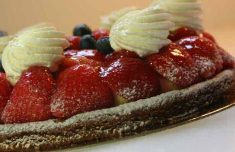 Aardbeiencroute gebakken op een korst van croûtedeeg, gevuld met banketbakkersroom, verse aardbeien en bosbessen en toefjes slagroom.