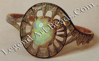 "It is a ""thistle leaf"" bracelet (1905-09) in gold and transparent enamel on coloured paillons with matrix opal."