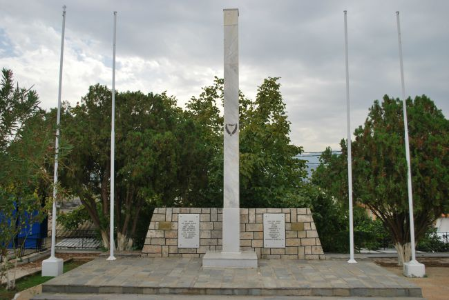 picture of monument in Plateia, Galatas, Crete with 4 flag poles, one for each nationality.