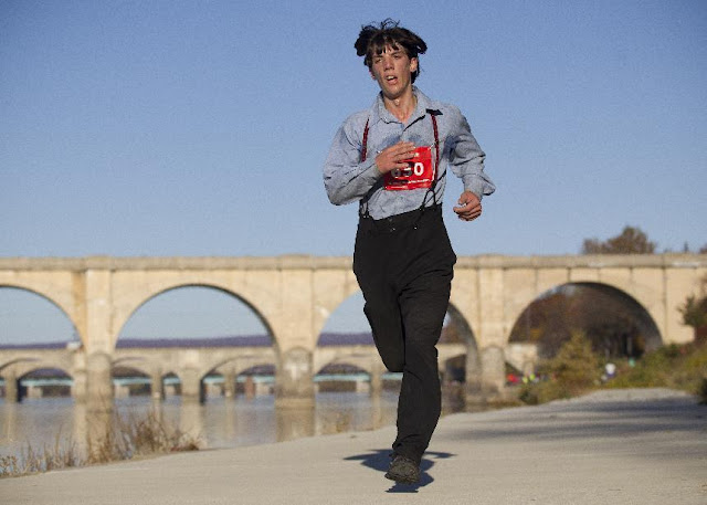 In this photo taken on Sunday, Nov. 8, 2015, Leroy Stolzfus, of Gordonville runs in the 2015 Harrisburg Marathon in Harrisburg, Pa. The Pennsylvania man turned heads as he whizzed by fellow runners at the Harrisburg Marathon, not because of his speed, but because of his unusual racing attire. Stolzfus finished the 26.2-mile race in just over three hours and five minutes — all while wearing his community's traditional clothing. (Daniel Zampogna /PennLive.com via AP) MANDATORY CREDIT