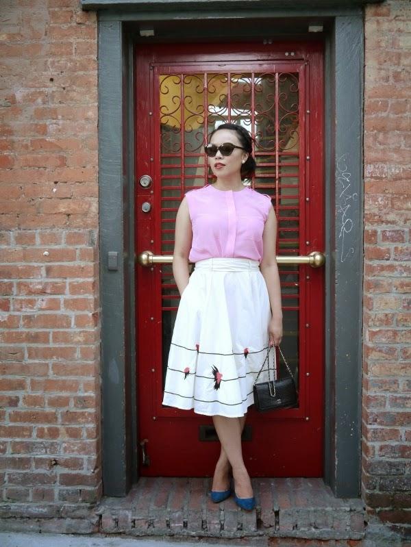 Pink blouse, bird-embellished midi skirt, turquoise heels