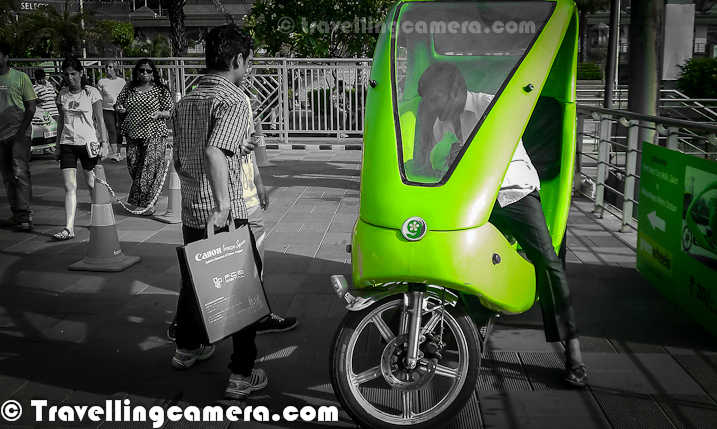 Recently Delhi's Chief Minister Sheila Dixit launched Green-Wheel Service at Saket. This is about running eco-friendly, battery powered & pollution free vehicles. Last weekend, I was at Select City Walk Mall of Saket and opted for Green-Wheel to reach Malviya Nagar Metro Station. Let's go through this Photo JOurney and know more about this lovely ride...As of now these are only launched in Saket and they run between Saket Malls & Malviya Nagar Metro Station. These Green-Wheels can be seen parked outisde Malviya Nagar Metro Station and Select City Walk Mall in Saket. They charge 20 Rs for one side and two people can sit at one point of time. Which means 10 rs per person, which is quite reasonable. Plan is to expand this service in other metro stations soon. Commuting from Malviya Nagar Metro to Saket Malls was one of the tedious thing. In fact, some time back when I went to Select City Walk via metro, I was surprised to know that Malviya Nagar Metro station is near as compared to Saket Station. Even the distance between Malviya Nagar and Saket malls is huge. So local transportation was one of the main pain point for folks commuting through Metro. G-Rik has solved this problem and hope that G-rik reach to other parts of Indian National Capital Region.These three-wheeler G-Riks were developed after extensive research and development by Green Wheels for over two years and has been fully customized to adapt to Indian conditions. Incidentally, Star Bus is the concessionaire for the first bus cluster launched in May 2011. At present, Delhi Metro runs feeder service as well on certain routes. This is besides the para-transit options like Gramin Sewa and autorickshaws. For more around this news, check out - http://articles.timesofindia.indiatimes.com/2012-04-28/delhi/31451728_1_bus-cluster-feeder-service-star-busThis photograph of Select City Walk Mall is clicked from G-Rik stand. It's located just at the exit of Parking. There is a counter on the corner from where one needs to take ticket for G-Rik ride. It takes around 7 minutes to reach Malviya Nagar Metro Station from Saket Malls. It seems that plan is to have around 5000 G-Riks in Delhi during next 15 months, which needs investment of around 100 crores.