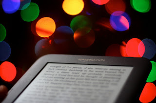 kindle e-reading device in front of christmas lights