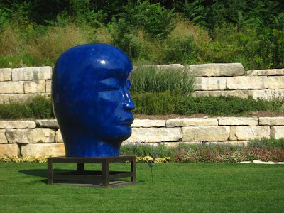 Cobalt blue giant head in a garden