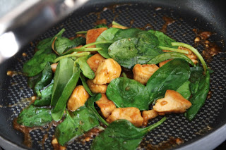 adding the spinach to chicken in skillet