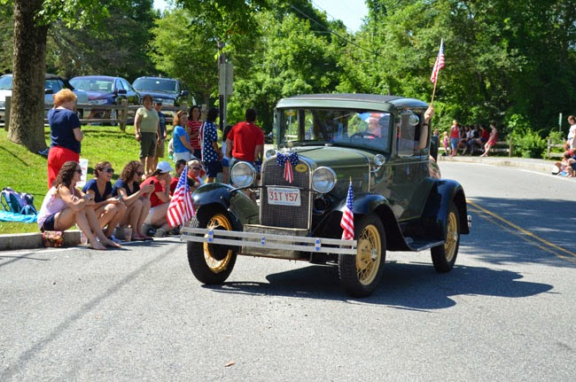 people watching an antique car parade