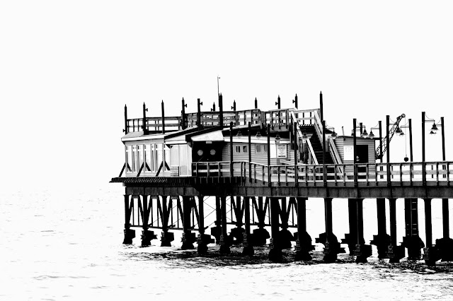 Black and white picture of wooden building on stilts, in water