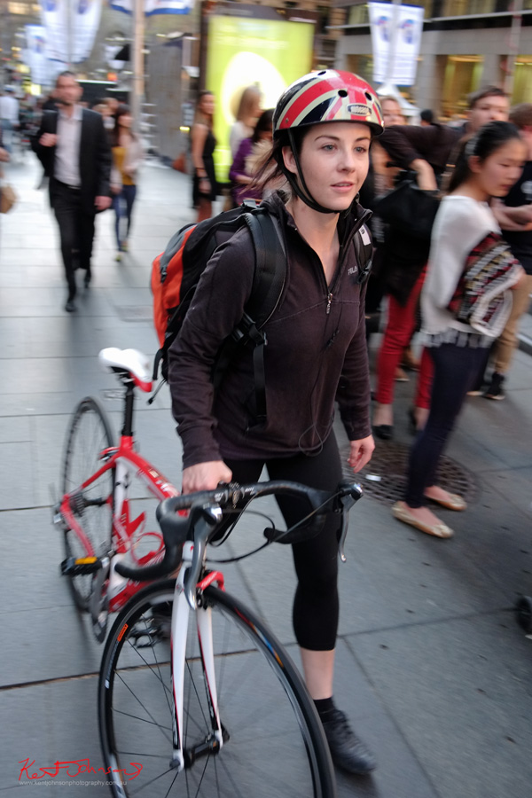 Bicycle commuter with red and white road bike, black tights, union jack cycling helmet.  Street Style Sydney, Martin Place Sydney. Fujifilm X-Pro1