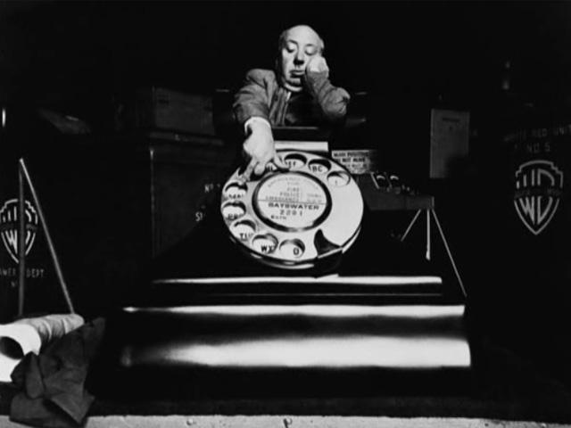 Hitchcock sobre la enorme maqueta del teléfono que usó en Crimen perfecto.