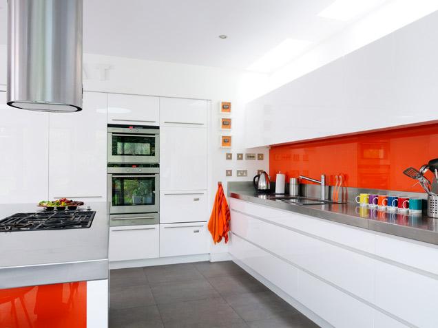 shiny orange backsplash pops against a sleek mix of stainless steel