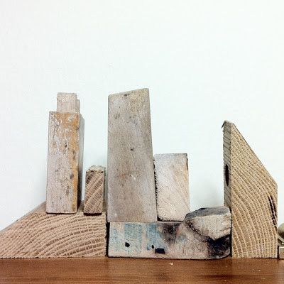 Wood off-cuts lined up in such a way that they resemble a city scape.