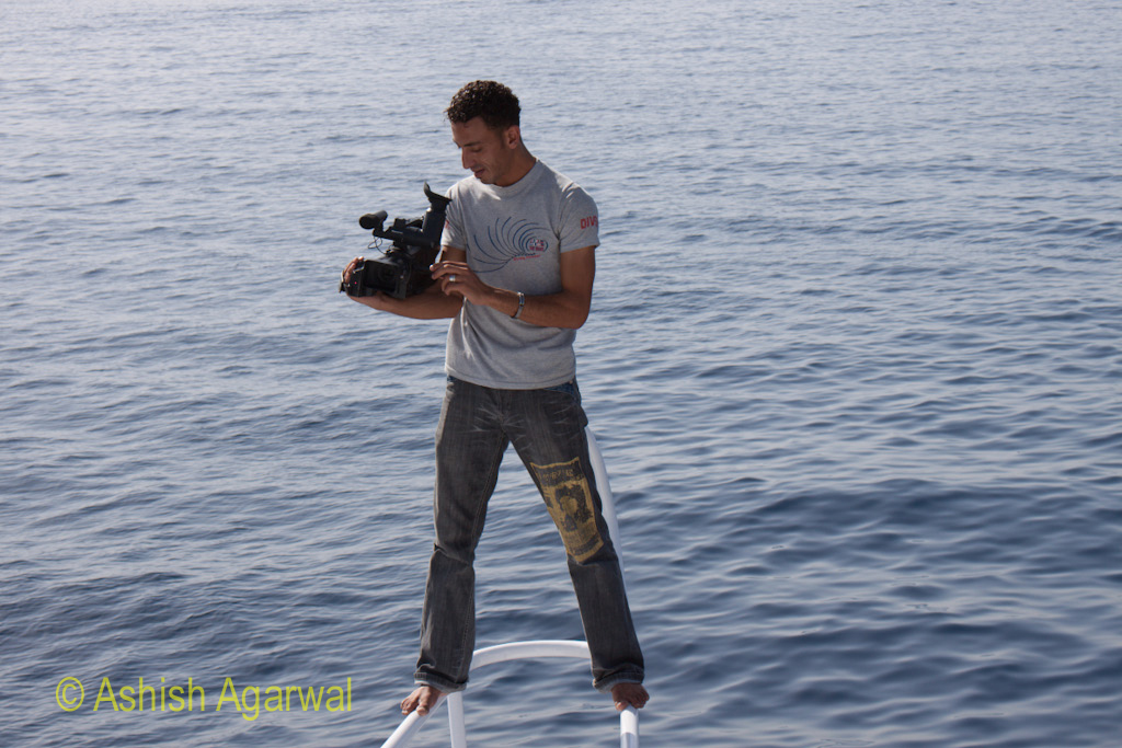 Young photographer standing on the railing of the ship while on the snorkeling trip in Sharm el Sheikh