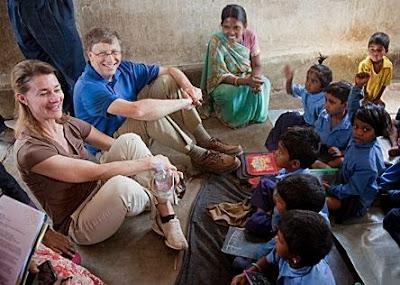 Foto de Bill Gates e sua esposa, Melinda, sentados no chão com outras crianças, todos sorridentes.