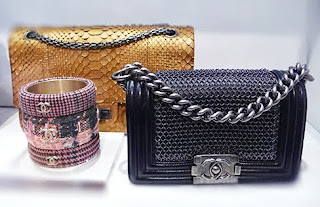 Mini reptile and chain link handbags and tweedy baubles from Chanel.