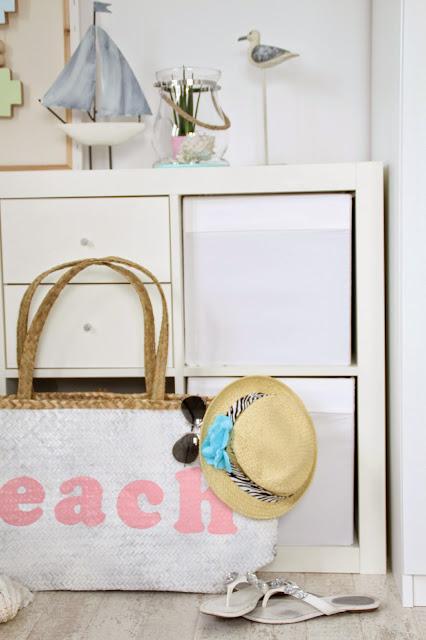 Weiße Kommode auf der mediterane Deko steht davor die Strandtasche mit Flip Flops