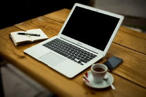 Portátil, libreta, móvil y café