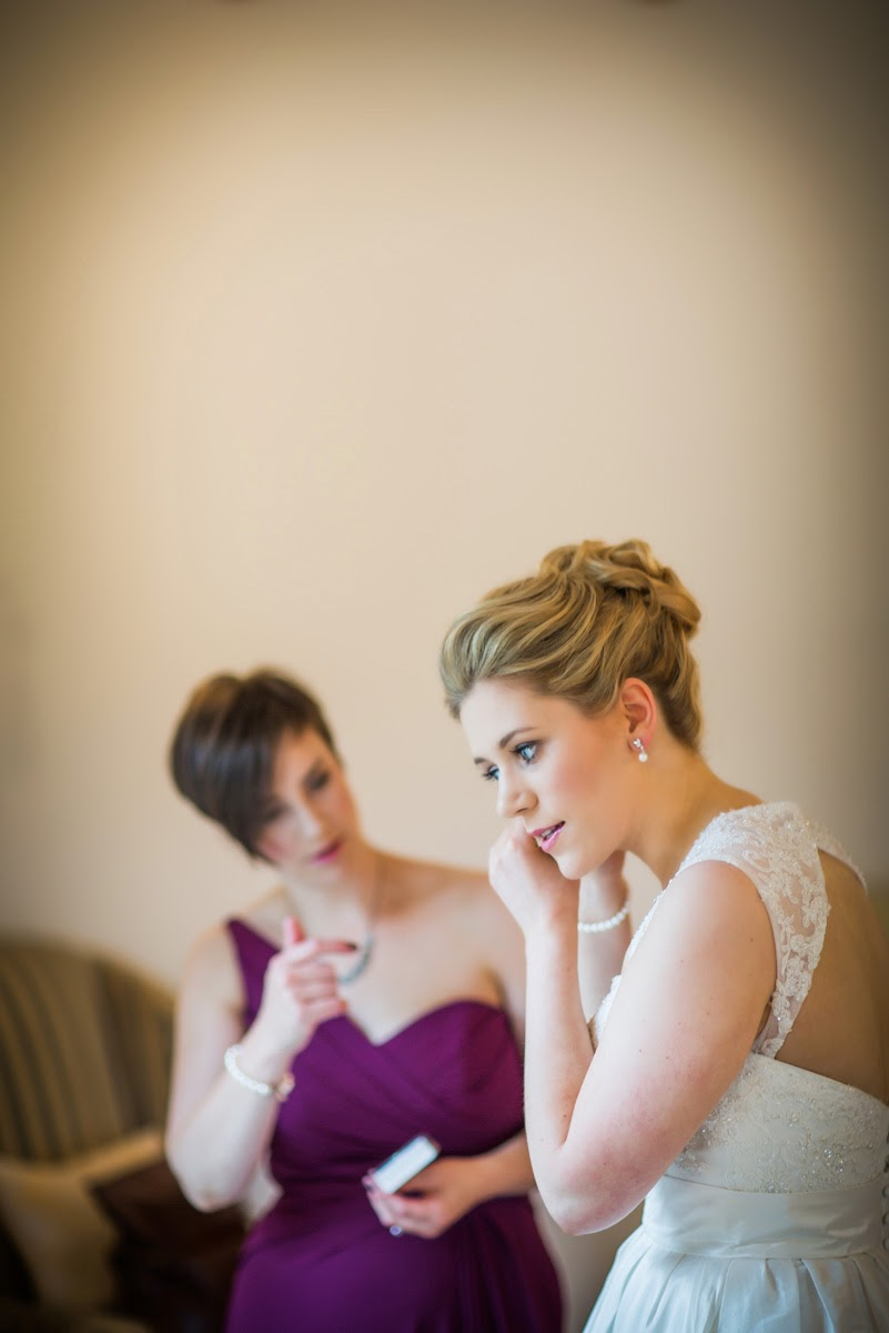 Alison adds the finishing touches to her bridal look with sparkly earrings