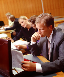 A team of people work on files in a courtroom.