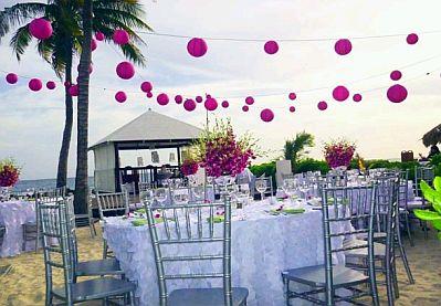 En esta propuesta tienes mesas con manteles blancos, sillas sin vestido y flores de color fucsia, el mismo color utilizado en las pantallas chinas colgadas