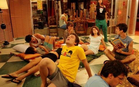 Escena del quinto episodio de la segunda temporada de la serie Con el Culo al Aire donde vemos a varios protagonistas tirados en el suelo del Bar pasando calor.