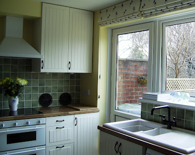 Mike and Rosie's white, green and yellow kitchen with touches of black and blue.