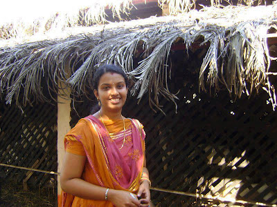Poor Girl from Tamil Nadu before her small hut but she looks very homely.
