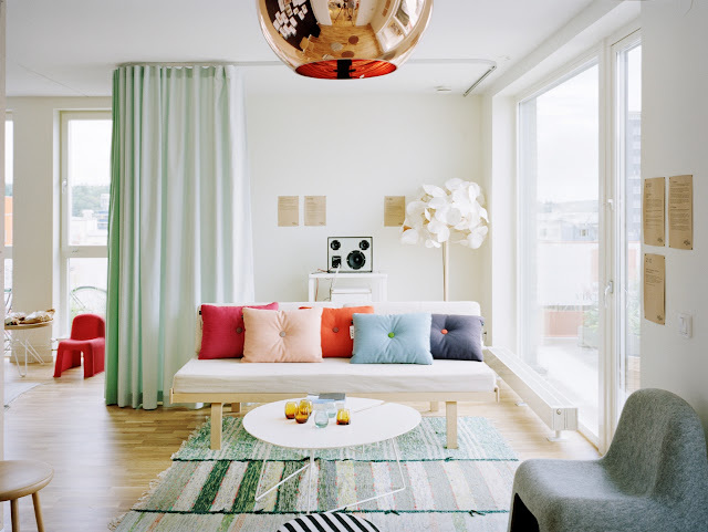 living room with mint green floor length curtains, copper tom dixon pendant, green and white striped rugs, wood floor, white sofa and brightly colored pillows