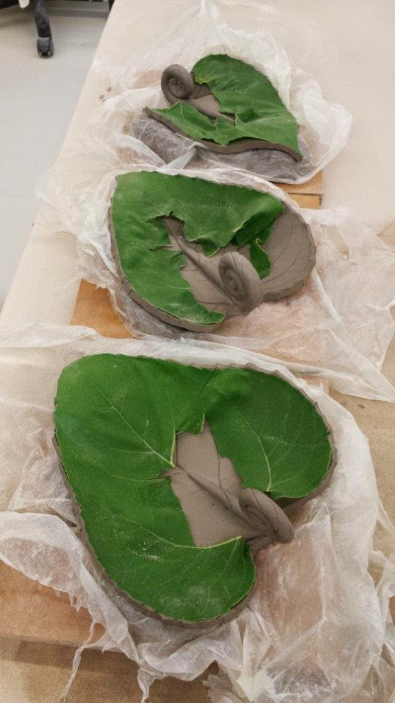 Handmade ceramic dishes made from pressed sunflower leaves, in progress.