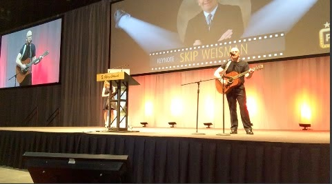 Skip Weisman, professional speaker debuts on guitar at end of recent keynote address in Calgary, Alberta in front of an audience of over 800.