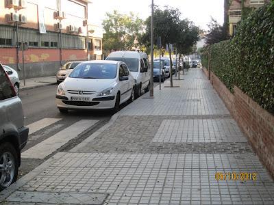 Vista de acerado con coches aparcados en cordón y vado con bandas señalizadoras de diferente textura pero poco contraste.