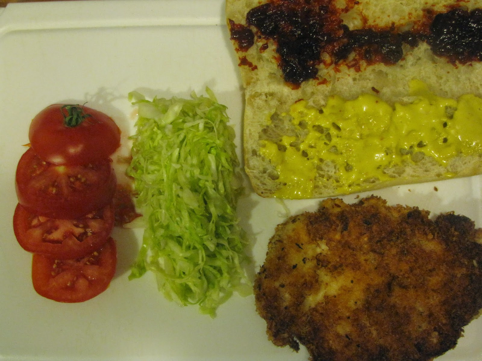 Tomato, cabbage, fried chicken and dressed ciabatta sandwich roll on a white chopping board