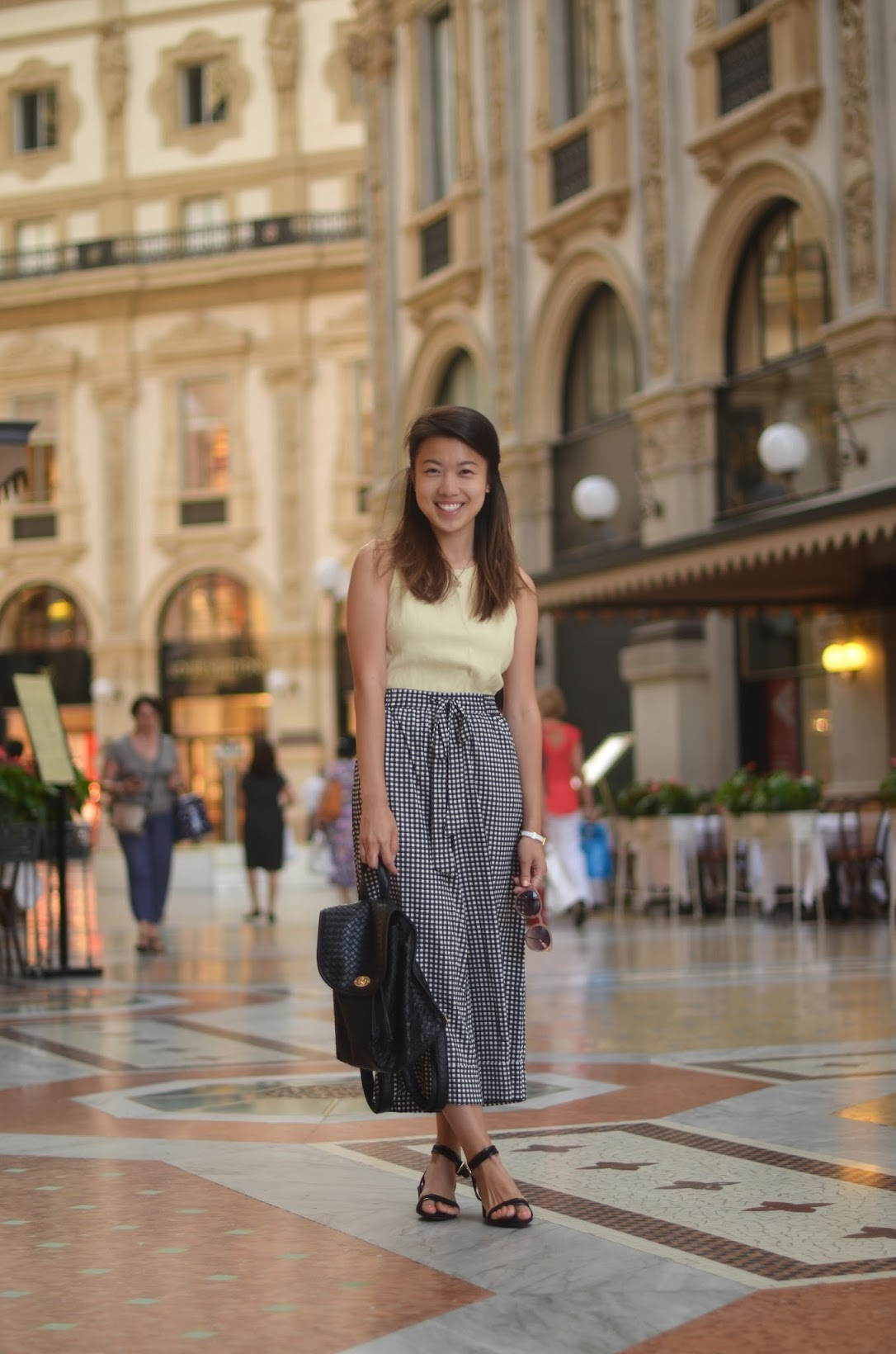 gingham culottes with yellow top, black sandals and mini backpack outfit in milan
