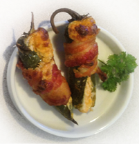 Close up of the bacon wrapped jalapeno popper. The bacon is crisp and cheese is bubbled and golden.
