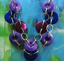 Chic double strand necklace has purple and blue buttons linked with silver chain loops and rings