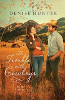 cover of Trouble with Cowboys by Denise Hunter shows a man and a woman near a fence in a hay field