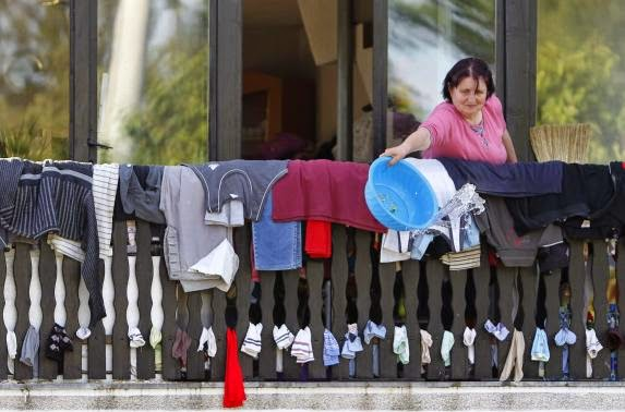 These 16 photos will disturb you... The Balkans in the grip of flood! - A woman throws away water as she dries clothes during heavy floods in Bosanski Samac May 19, 2014.