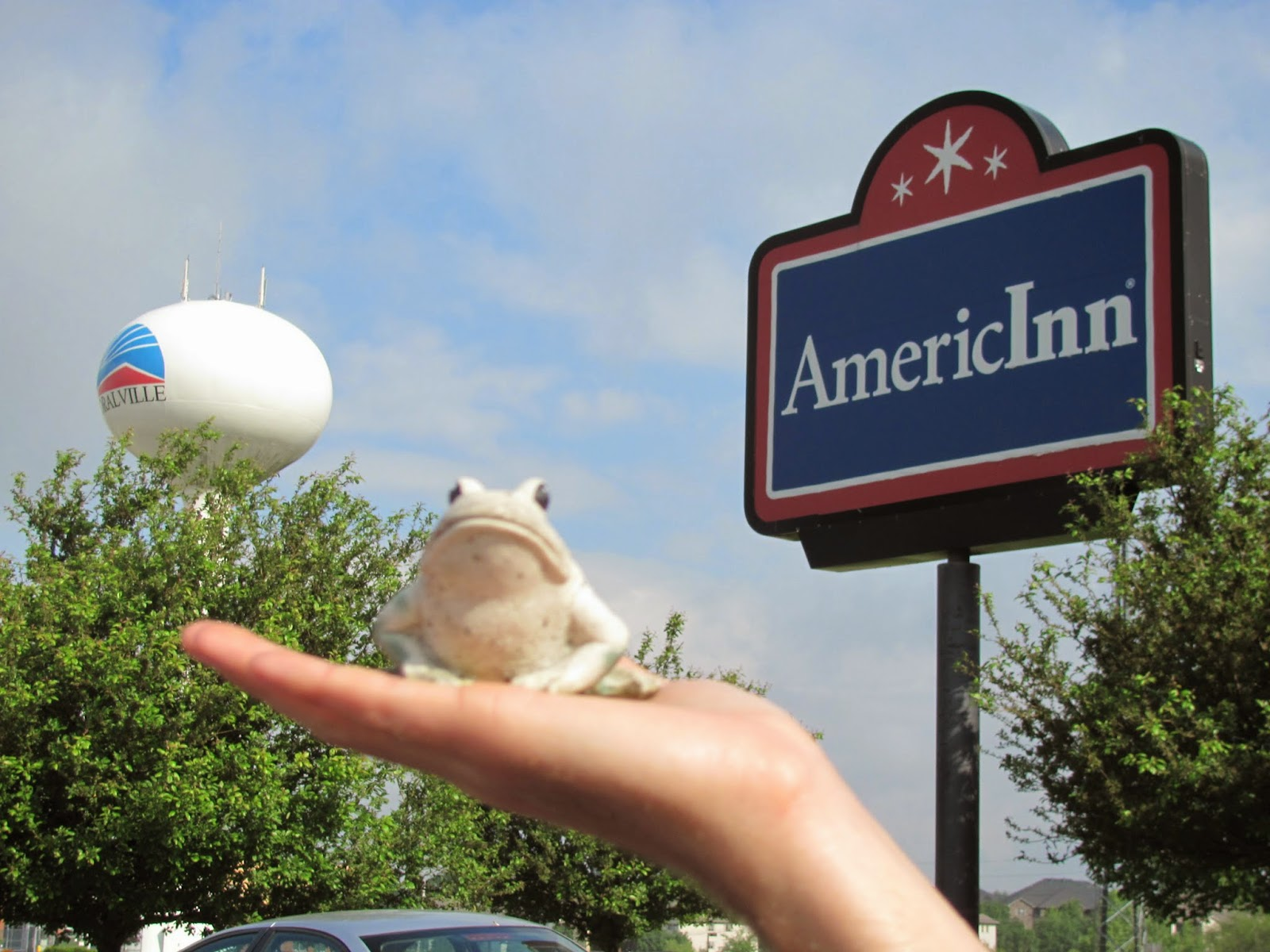 Frog poses before the AmericInn sign and the Coralville water tower