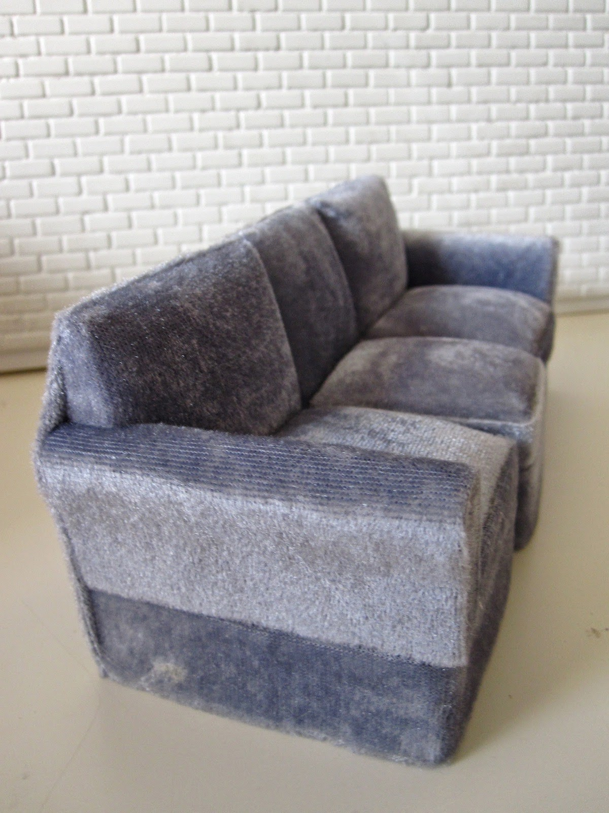 Modern miniature three seater grey velvet sofa.