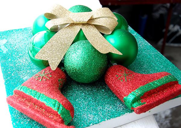 Green glitter canvas, green ornaments, gold ribbon, red and green skates upclose