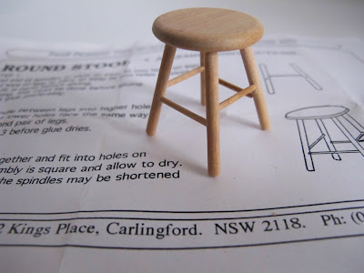 Wooden dolls' house miniature stool, sitting on the kit instruction sheet.