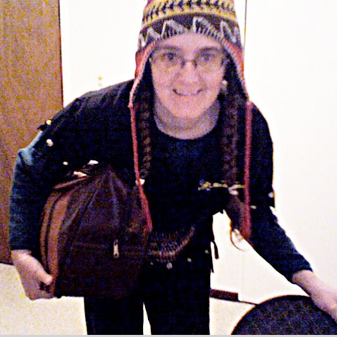 Cynthia M. Parkhill leans into frame of picture, wearing beaded and fringed black bowling shirt, red-patterned hat with earflaps and carrying bowling ball in brown bag under her right arm.